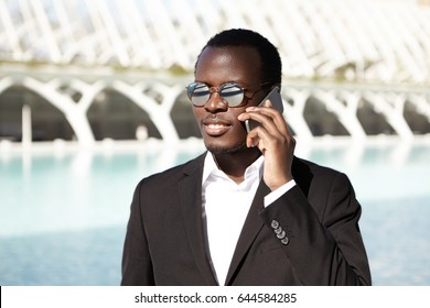 Trendy young handsome businessman having pure dark skin and full lips dressed formally going to work making appointment over telephone having shining smile and white teeth being happy of his success