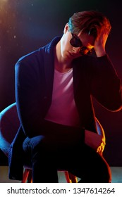 Trendy young man with cool hairstyle wearing black jacket with sunglasses. High Fashion male model in colorful bright neon lights posing on black background. Art design concept