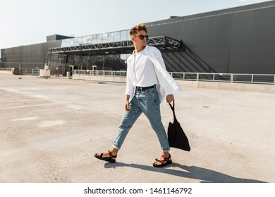 Trendy young man hipster in stylish white and denim clothes in vintage sandals with a black cloth bag walks outdoors on a sunny day. Modern guy in sunglasses in the city. Summer fashionable menswear.