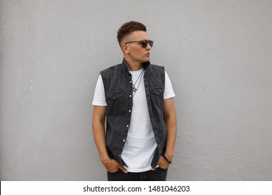 Trendy young man hipster in a vintage denim vest in a white T-shirt in jeans in sunglasses posing near the wall on the street on a summer day. Attractive urban guy model in the city. Street fashion.