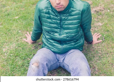 A trendy young man with a hole torn in his jeans at the knee is sitting on the grass