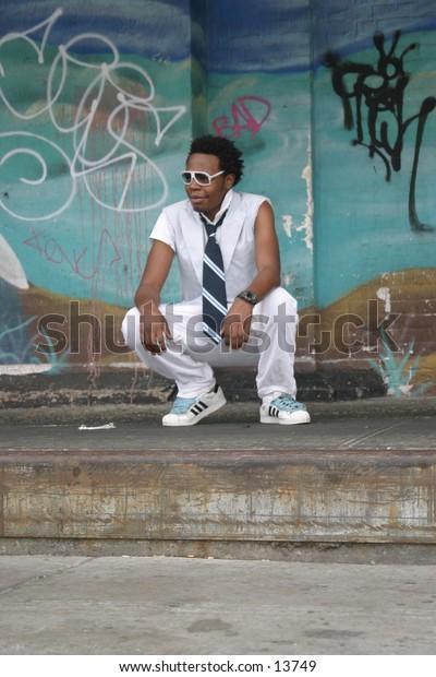 trendy young man near graffiti wall