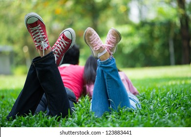 Trendy young people in sneakers lying on the grass and enjoying summer days