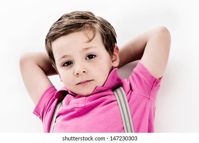 Trendy young toddler boy, lying down on studio white background. Looking to camera with his hands behind his head. Isolated on a white background.