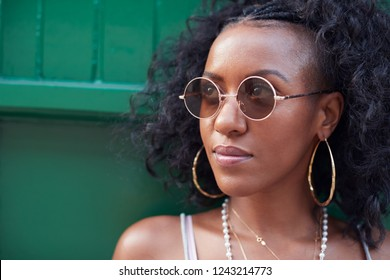 Trendy young woman in camisole and sunglasses and jewellery