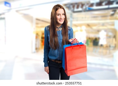 Trendy young woman with different colors shopping bags. Over shopping center background