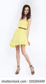 Trendy young woman in funky yellow dress smiling against white background