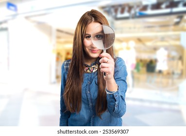Trendy young woman with a magnifying glass in front of her eye. Over shopping centre background