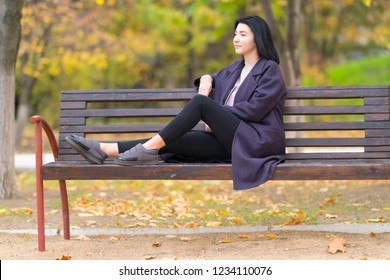 Trendy young woman relaxing on a rustic wooden bench in a park staring thoughtfully off to the side in autumn with colorful foliage behind her