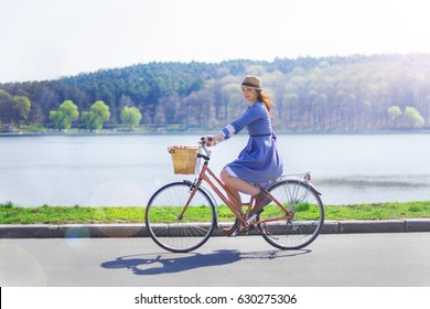 Trendy young woman stop to riding on her vintage bike with basket of flowers while focused chatting or talk on smart phone outside,gorgeous female using mobile phone during recreation time in the park