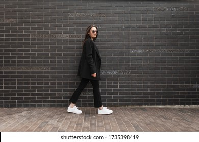 Trendy young woman in stylish jacket in vintage jeans in white sneakers in sunglasses walks near brick wall in city. Attractive girl in casual black clothes is walking on street. American style.