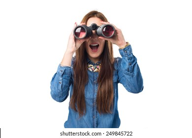 Trendy young woman using binoculars. She looks surprised. Over white background