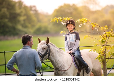 Trentham, Stoke on Trent, Staffordshire - 1st August 2018 - A little boy with Autism, ADHD, Aspergers Syndrome, riding a horse with an instructor in the beautiful countryside, mental health, illness