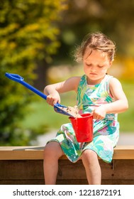 Trentham, Stoke on Trent, Staffordshire - 1st July 2017 - A cute little girl puts sand into a bucket ready for building sandcastles on a warm sunny day