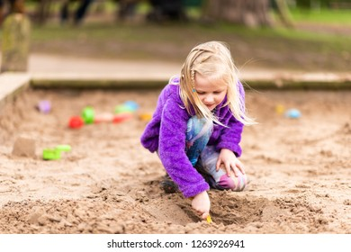 Trentham, Stoke on Trent, Staffordshire - 21st December 2018 - A pretty little girl plays in the sand pit, digging holes and making sandcastles