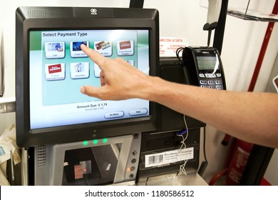 Trento, Italy - JUL 11, 2018: A man is paying on self-service cash desk in supermarket