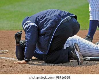 TRENTON, NJ - APRIL 11: A Trenton trainer tends to a player who had been hit in the head by a pitch moments earlier against the Sea Dogs April 11, 2012 in Trenton, NJ.