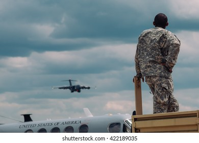Trenton,NJ - May 15 2016: At a free air show at McGuire AFB, a soldier watches on as a large air force plane lands.