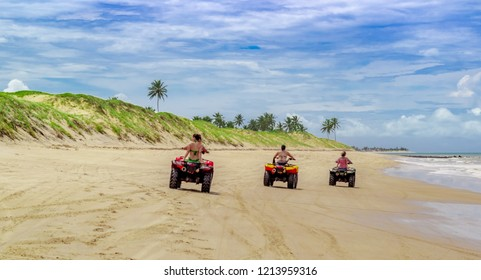 tres quadricycles in a row on the sand of the beach