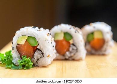 Tres Sushis Uramakis de arroz con atun, aguacate y esparragos trigueros sobre base de madera clara y fondo oscuro