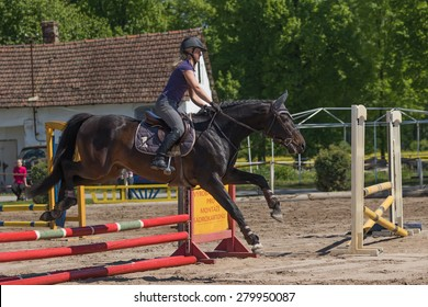 """TRESTINA, CZECH REPUBLIC - MAY 16: Blonde young horsewoman is jumping over the hurdle at """"Equestrian Hobby Series 2015"""" on May 16, 2015  in Trestina, Czech Republic."""