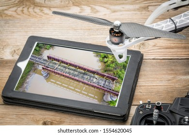 trestle of abandoned railway across a river - reviewing an aerial image on a digital tablet with drone propeller and radio controller,