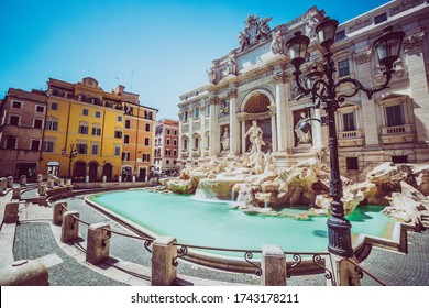 Trevi Fountain in Rome with nobody. Monument in one of the many landmarks in the capital of Italy. No person present. Sky cloudless. Lamppost in the foreground.