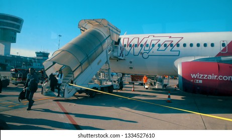 Treviso, Italy - circa Jan, 2018: Passengers step off jet airplane using stairs at arrival to Treviso airport in Italy