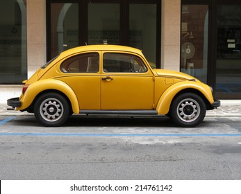 TREVISO, ITALY - CIRCA JULY 2014: Yellow Volkswagen Beetle vintage car parked in a street of the city centre.