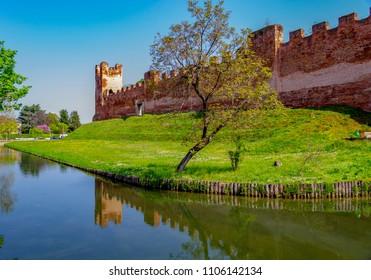 TREVISO, VENETO, ITALY - April 9, 2017: Castelfranco Veneto castle walls are reflected in the waters of the  Avenale River.