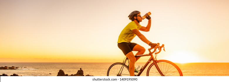 Triahtlon athlete man drinking water bottle on road racing bike ride outdoors at sunset banner panorama landscape. Cyclist biking outside with sunglasses and helmet.