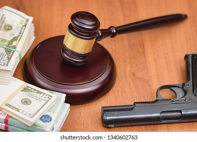 Trial for robbery with murder. Murder and robbery of businessman and the court. Money, gun and judge's gavel on the table.