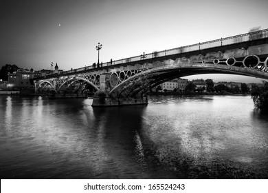 Triana bridge over the river Guadalquivir, Sevilla, Andalucia, Spain. Black and White.