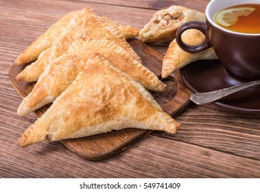 Triangle meat pies with cup of tea .