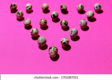 A triangle of quail eggs is upside down on a textured pink background. The top of the triangle in the foreground. Conceptual bright photo for your design.