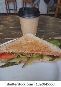 Triangle sandwich and takeaway cup on table in cafe