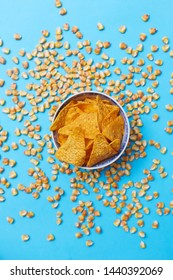 Triangle shaped nacho chips in a bowl surrounded with corn beans on pastel blue background