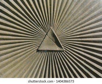 triangle and sumbeam as a symbol for the eye of providence carved in an old marble stone