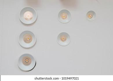 Triangle of white glowing light bulbs.