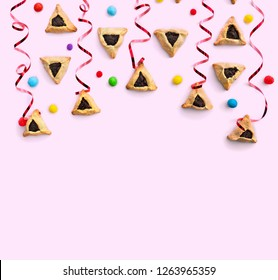 Triangular cookies with poppy seeds ( hamantasch or aman ears ), colored candy and red serpentine for jewish holiday of purim celebration on pink background with space for text. Top view, flat lay