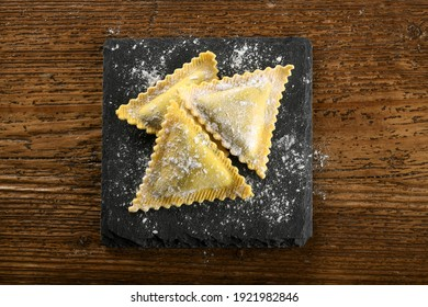 Triangular fresh handmade raw filled ravioli Italian pasta on a board drizzled with flour viewed top down on a wood table