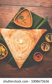 Triangular Paper Masala dosa is a South Indian meal served with sambhar and variety of coconut chutney . Selective focus