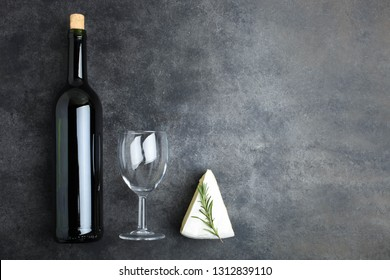 Triangular piece of white Camembert chees with bottle of wine and glass on black background. Top view, copy space. Concept serving of cheese.
