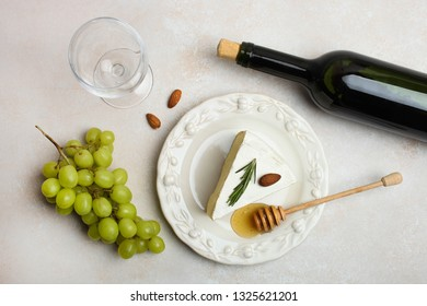 Triangular piece of white Camembert cheese with honey on white plate and bottle of wine with grapes on neutral background. Top view. Concept serving of cheese.