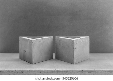 Triangular planters made of natural concrete on concrete background
