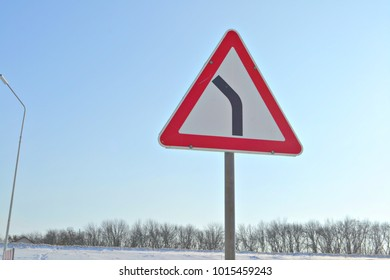 Triangular road sign indicating a bend in the road.