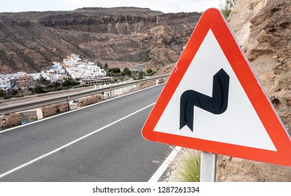 A triangular road warning sign warning of bends ahead on a hillside road high in the hills of Gran Canaria. The town of Mogan is visible in distant valley.
