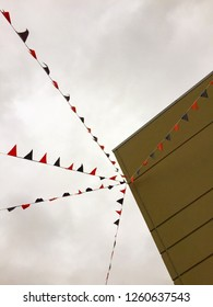 Triangular shaped bunting flags strung out from side of building under a dreary overcast flat sky.