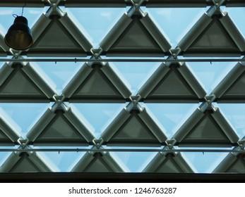 triangular shaped skylight shade elements in a modern building under glass skylight on steel frame under blue sky
