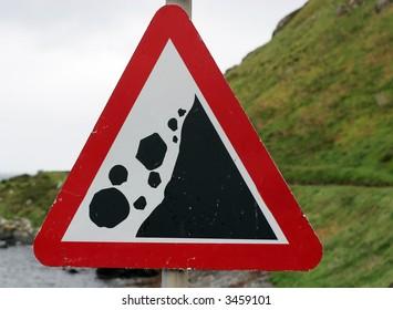 triangular sign with symbols indicating falling rocks